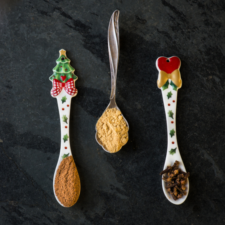christmas ground: Spices for Christmas Gingerbread Cookies in Spoons on the Dark Grunge Background. Ground Cinnamon, Cinnamon Sticks, Ginger, Cloves, Nutmeg