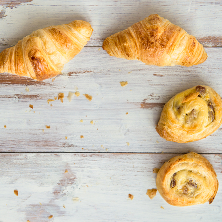 pains: Freshly Baked French butter Pastries on the Old Wooden Background. Croissants, pains au chocolat, pains aux raisins. Shallow DOF, Selective Focus