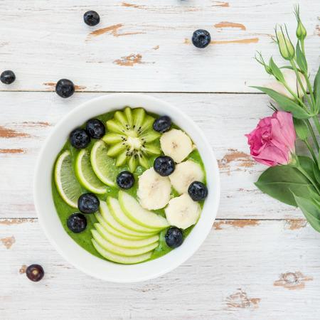 Gezonde groene smoothie in de kom van banaan en spinazie met bosbessen, limoen, appel en kiwi bovenaan, bovenaanzicht, bloemen in de buurt