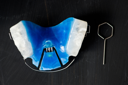 crooked teeth: Dental Blue Removable Braces or Retainers for Teeth, Orthodontic on Dark Grey Background