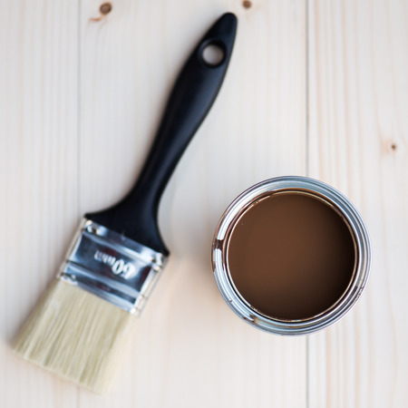 redecorating: House Renovation, Brown Paint Can and Brush on Wooden background Stock Photo