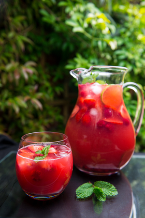 Very Red Fresh Homemade Strawberry and Raspberry Lemonade with Ice Cubes, Mint and Lime in Glass Jar on Green Background