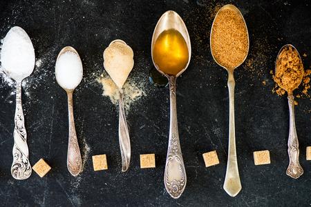 Verschillende soorten suiker in de lepels, zoals kokos suiker, pure rietsuiker, poedersuiker, agave siroop, donkere basterdsuiker, gouden basterdsuiker, demerara kubussen Stockfoto