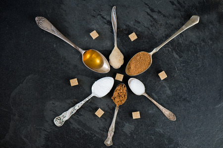 Different Kinds of Sugar in the Spoons, such as coconut sugar, pure cane sugar, icing sugar, agave syrup, dark brown soft sugar, golden caster sugar, demerara cubes