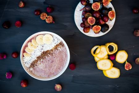 flax seeds: Healthy Banana and Strawberries  Smoothie in the Bowl decorated with Frozen Cherries, Desiccated Coconut Shreds, Flax Seeds on Dark Background