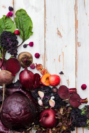 Verzameling van verse paarse groenten en fruit zoals pruimen, bieten, uien, aubergine, sla, kool, bonen, vijgen, druiven op de witte achtergrond met bovenaanzicht
