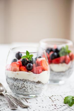 Layered Light Healthy Dessert (pudding) Chia Seeds in yoghurt, yoghurt en aardbeien, bosbessen en munt in de glazen kommen