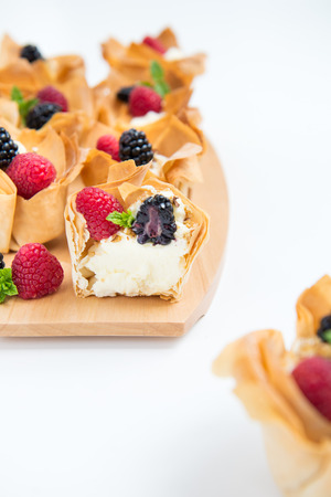 filo: Homemade Filo Pastry Baskets with Mascarpone Cream, Berries, Walnut Pieces and Mint, White Background Stock Photo