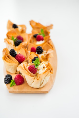 filo: Homemade Filo Pastry Baskets with Mascarpone Cream, Berries, Walnut Pieces and Mint, White Background, Space for text Stock Photo