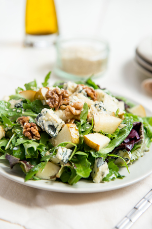 Healthy Salad made from Green Salad Leaves, Rocket Salad, Slices of Fresh Pears, pieces of Blue Cheese, Walnuts and Sesame Seeds Stock Photo