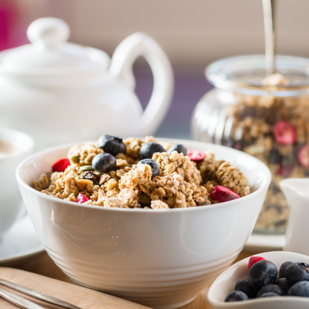 Protein Granola made from Oat Porridge, Nuts, Seeds, Berries in the Bowl with Table set for Breakfast