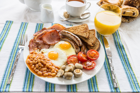 Traditional Full English Breakfast with sunny-side-up fried eggs,  bacon, sausages, beans in tomato sause, toasts,  fried tomatoes and mushrooms. Also, with Tea, Orange Juice and Puff Pastry.
