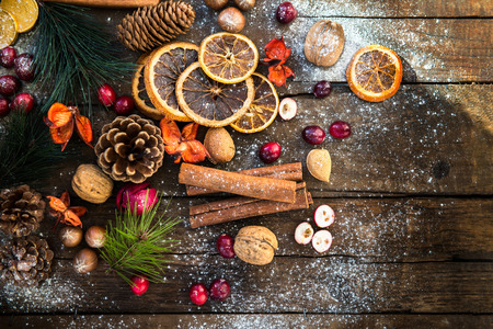 Preparation for the Christmas with lots of Xmas Symbols such as snow, nuts, orange slices, tree branches, cranberries, cinnamon sticks, cones on Wooden Rustic Background
