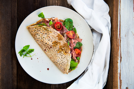 parma ham: Savoury Buckwheat Pancakes with Cherry Tomatoes, Rocket Salad, Spinach, Parma Ham, on Dark Rustic Wooden Background
