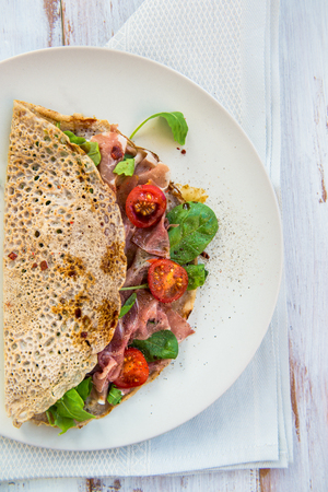 parma ham: Savoury Buckwheat Pancakes with Cherry Tomatoes, Rocket Salad, Spinach, Parma Ham, on White Wooden Background