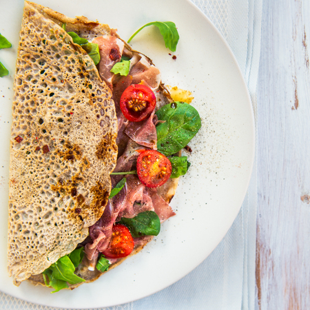 Savoury Buckwheat Pancakes with Cherry Tomatoes, Rocket Salad, Spinach, Parma Ham, on White Wooden Background