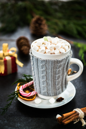 Christmas Setting with Hot Chocolate and Marshmallows in a Fancy Sweater Mug with Candy Cane, Xmas Tree, Cinnamon Sticks and other decoration on the Background