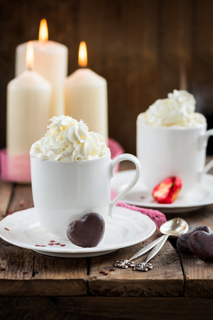 Hot Tea or Chocolate in White Cups with Chocolate Hearts and Lit Candles on Wooden Rustic Background, Valentines Day Concept