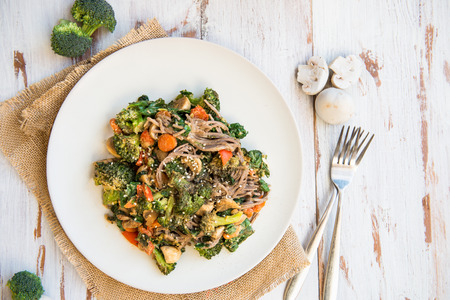 Healthy Warm Detox Salad from Soba  (Buckwheat) Noodles, Broccoli, Spinach, Carrots and Mushrooms. Top View, Light Background Stock Photo