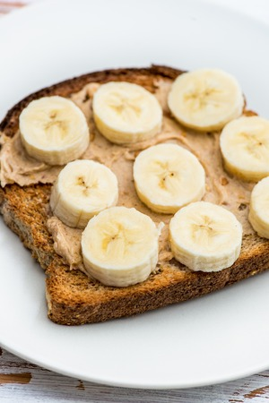 banana bread: Healthy Snack Alternative made from Toasts from Wholewheat Bread with Peanut Butter and Banana with Cinnamon, Light Background