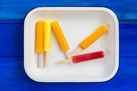 popsicles: Ice Orange, Strawberry and Lemon Popsicles in the Tray on Blue Background Foto de archivo