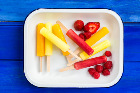 popsicles: Ice Orange, Strawberry and Lemon Popsicles with Berries in the Tray, on Blue Background