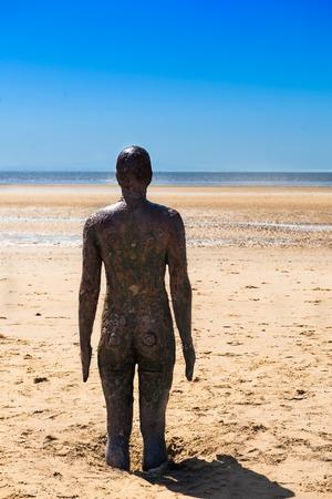 CROSBY BEACH, ENGELAND - MEI 16, 2016: Beeldhouwwerk op Crosby Beach vormt een deel van de Another Place moderne kunstinstallatie door Anthony Gormley Stockfoto