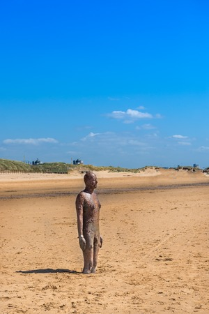 CROSBY BEACH, ENGLAND - MAY16, 2016: Sculpture on Crosby Beach forming part of the Another Place modern art installation by Anthony Gormley
