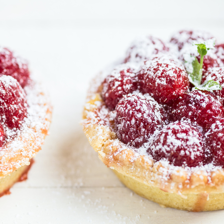 jam tarts: Raspberry Tarts with Mint Leaves and covered with Icing Sugar on White Background