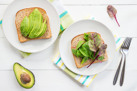 benedict: Healthy Breakfast with Wholemeal Bread Toast with Green Salad and Avocado, Top View. Table set for the Eggs in Clouds, which are an oven dish, when the egg white and egg yolk are cooking separately.