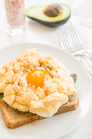 Healthy Breakfast with Wholemeal Bread Toast and Cloud Egg with Green Salad and Avocado. Egg in Clouds is an oven dish, when the egg white and egg yolks are cooking separately.