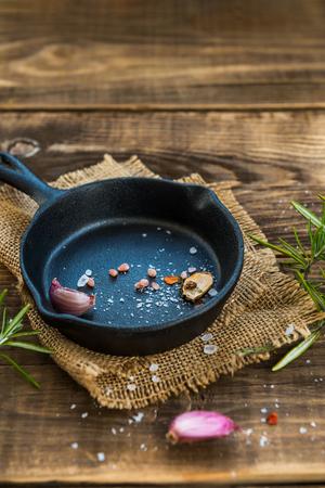 素朴な木製の背景にスパイスと鋳鉄のフライパン