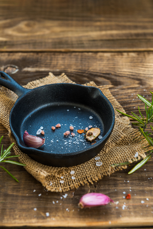 Cast-iron Frying Pans with Spices on Rustic Wooden Background Imagens