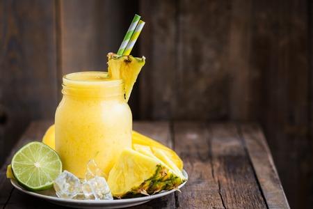 Slushy van de zomer van Mango, Ananas, Kalk en Ijs met sommige ingrediënten dichtbij op donkere rustieke achtergrond