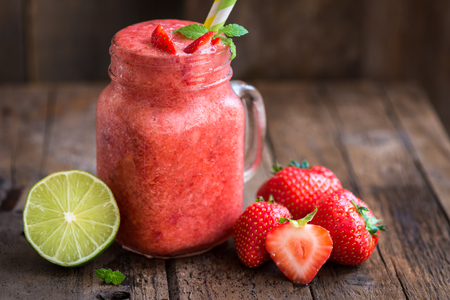Summer Slushy from Strawberries, Lime and Ice with some ingredients nearby on dark rustic background Stock Photo
