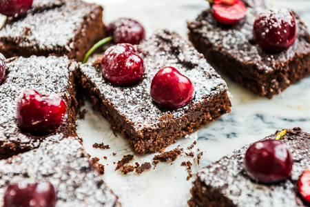 Healthy Double Chocolate Brownies with Cherries. Made from Banana, Wholewheat and Coconut Flour and Maple Syrup. Vegan concept. Top View, marble background