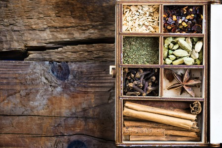 Box with variety of dried spices, such as ginger, mint, clove, chili flakes, cardamon, star anise, cinnamon sticks on dark rustic wooden background