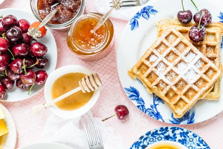 Table Set for Breakfast with different kinds of Healthy Waffles, Jams and Berries