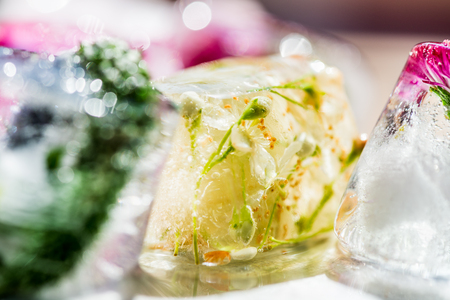 Frozen Spring Flowers in Ice Cubes on Light Background