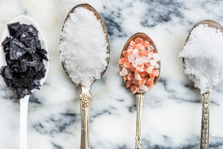 Different Kinds of Salt in Spoons, such as Himalayan Pink, Sea Original, Iodised Table, Sea Salt Flakes, Pink Diamonds, Black Sea Flakes, on Light Marble Background