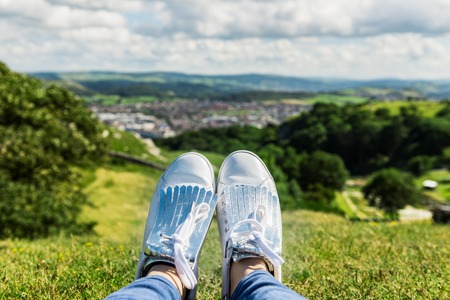 milánó: Yound Woman in White Sneakers is relaxing on the Hill with Beautifull View on the city of Llandudno in Nothern Wales during Nice Summer Day
