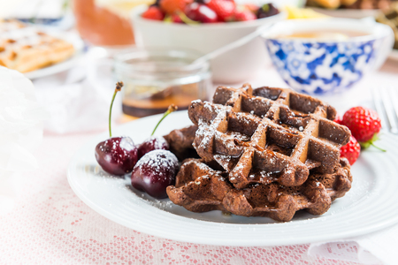 Table Set for Breakfast with Chocolate Banana Waffles. Honey, Strawberries and Cherries nearby Stock Photo