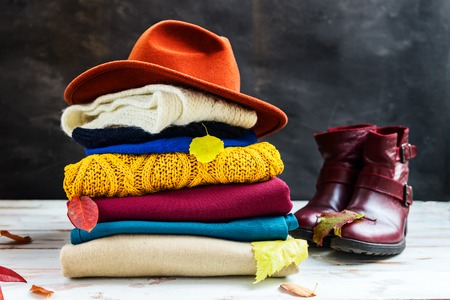 Stack of colorful warm autumn and winter clothes on dark background