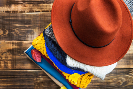 Stack of colorful warm autumn and winter clothes, top view, wooden rustic background Reklamní fotografie