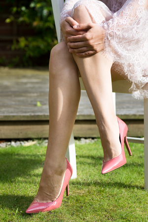 Girl showing her legs in white lace dress and pink court shoes on the green nature background Stock Photo