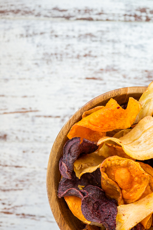 Bowl of Healthy Snack from Vegetable Chips, such as Sweet Potato, Beetroot, Carrot, Parsnip on Light Wooden Background