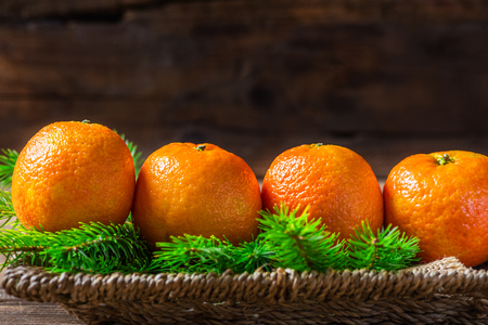 clementines: Fresh Clementines or Tangerines and Xmas Tree Branches in the Basket on Brown Wooden Table  Stock Photo
