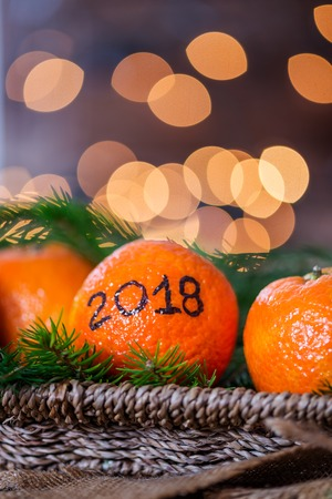 Nieuwjaar 2018 is Coming Concept. Nummers geschreven in zwarte inkt op de sinaasappelen die in de mand met Pine Sticks en Xmas Lights op de achtergrond liggen Stockfoto