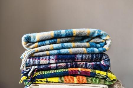 Stapel wollen gecontroleerde dekens, de herfst en de winterconcept Stockfoto