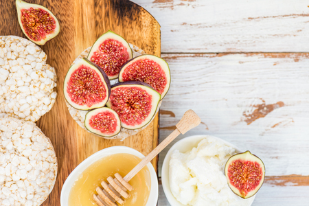 Healthy snack from Rice cake or crackers, figs and ricotta cheese on light wooden background